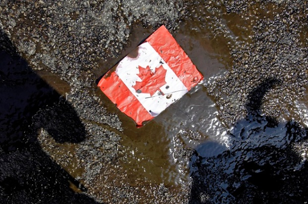 A placard with the Canadian flag rests on the ground covered in oil as demonstrators conduct a die-in to protest against the Keystone Pipeline and the Alberta Tar Sands outside of the Canadian Consulate in downtown Chicago, Thursday, May 17, 2012. (AP Photo/ Nam Y. Huh)
